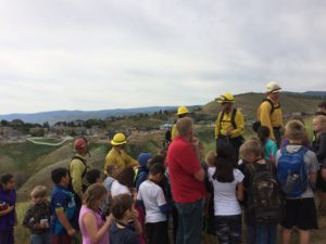 Image of firemen with students on a hike