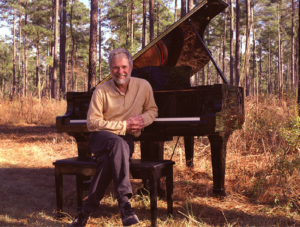 Image of Rolling Stones keyboardist Chuck Leavell sitting next to a piano in the woods