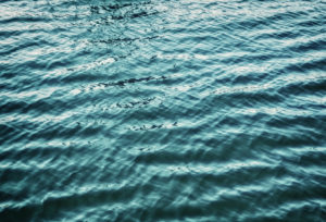 image of ripples in a body of blue water